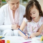 Portrait of cute girl drawing with colorful pencils with her grandmother near by