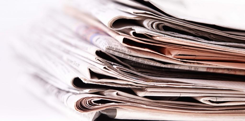 International newspapers on white background. Beautiful shallow dof.