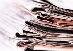 International newspapers on white background. Beautiful shallow dof.