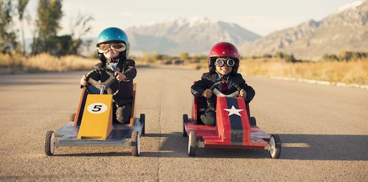 Two young businessmen dressed in business suits and sitting in homemade box cars are ready to race for more business. Both boys are wearing helmets and goggles racing on a road in Utah, USA.