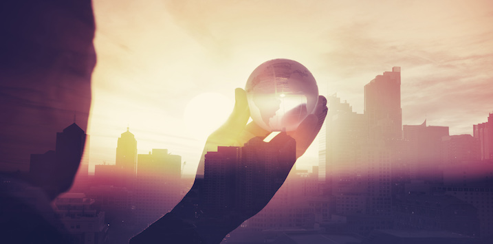 Business man in suit with cityscape montage. The man is unrecognizable and you cannot see his face. He is superimposed onto a city skyline at sunset. He is holding a world map globe like a crystal ball. Success, vision concept with copy space.