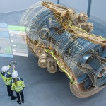 Industry 4.0 Two Engineers Standing and Talking in Factory Workshop with Augmented Reality 3D Model Concept of Giant Turbine Engine. Graphics Visualization. High Angle Shot. VFX Special Visual Effects
